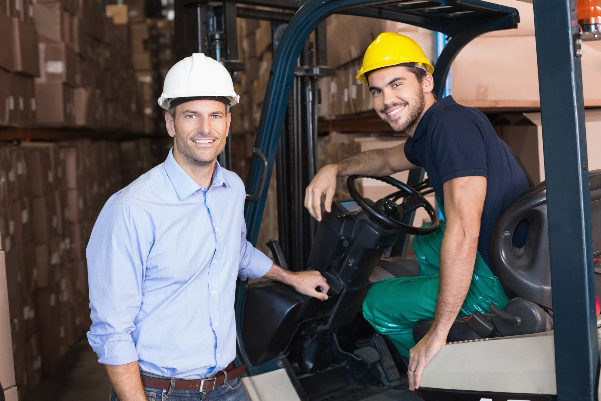 Warehouse manager smiling at camera with forklift driver in a large warehouse